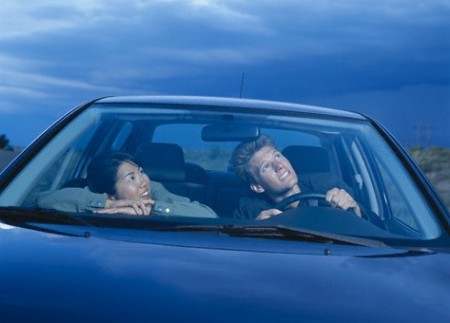 Young Couple in Car Looking Up