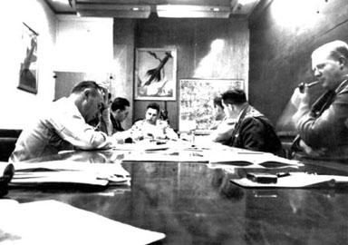 """Le groupe du projet Sign dans la salle de conférence du département T-2 à Wright Patterson, en 1948. A partir de la cauche et de la table on trouve : le lieutenant-colonel Malcolm Seashore, chef de l'Analyse Technique du Renseignement du Commandement du Matériel, une personne non-identifiable masquée par Seashore, le lieutenant-colonel J. J. Hausman, Howard McCoy ; [ce qu'on pense être] le capitaine Robert Sneider, Officier de Projet sous McCoy et Clingerman, [ce qu'on pense être] le colonel William Clingerman, officier executif pour l'Analyse du Renseignement du Commandement du Matériel (MCIA) et John """"Red"""" Honaker, liaison avec Twining, tenant sa pipe The Sign historical group"""